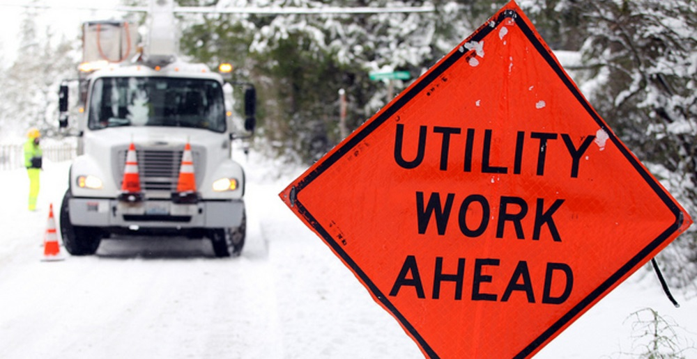 Sign warns of utility work ahead, with a utility truck covered in snow in the background.