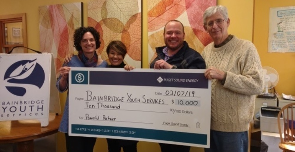 PSE community and outreach leads stand holding a check for Bainbridge Youth Services