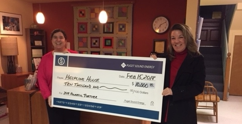 Karen Brubeck and Maria Metzler stand holding a check to Helpline House.