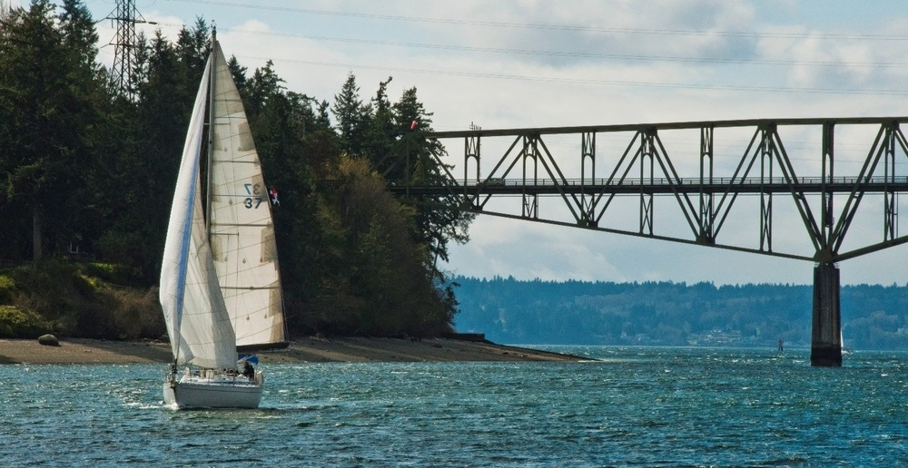 Sailboat moves under the Agate Pass bridge on a sunny day with small waves.