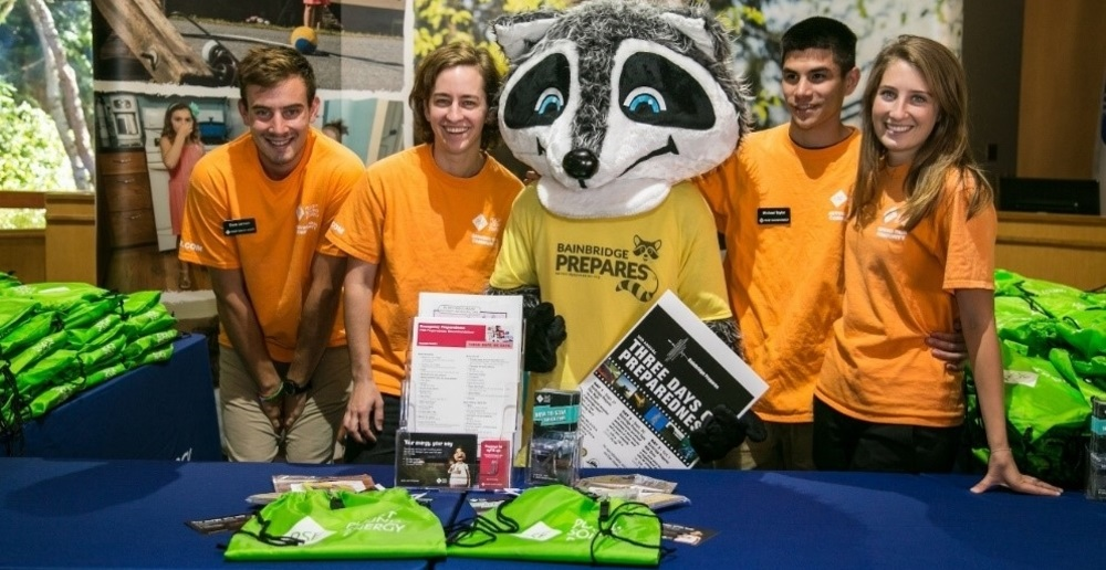 Four people sitting behind a PSE branded table with Ready Raccoon mascot holding PSE materials