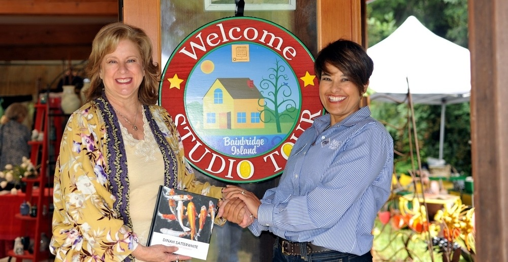 Dinah Satterwhite, Studio Tour Manager and Renee Zimmerman, PSE Community Projects Manager shaking hands, holding a book. They are standing in front of a sign that reads welcome studio tour Bainbridge Island.