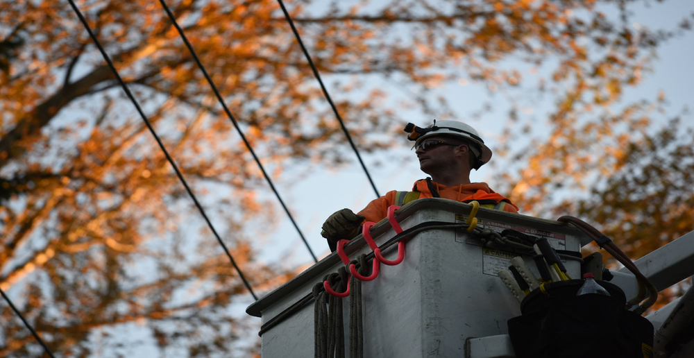 PSE lineworker looking at overhead transmission lines from bucket truck arm.
