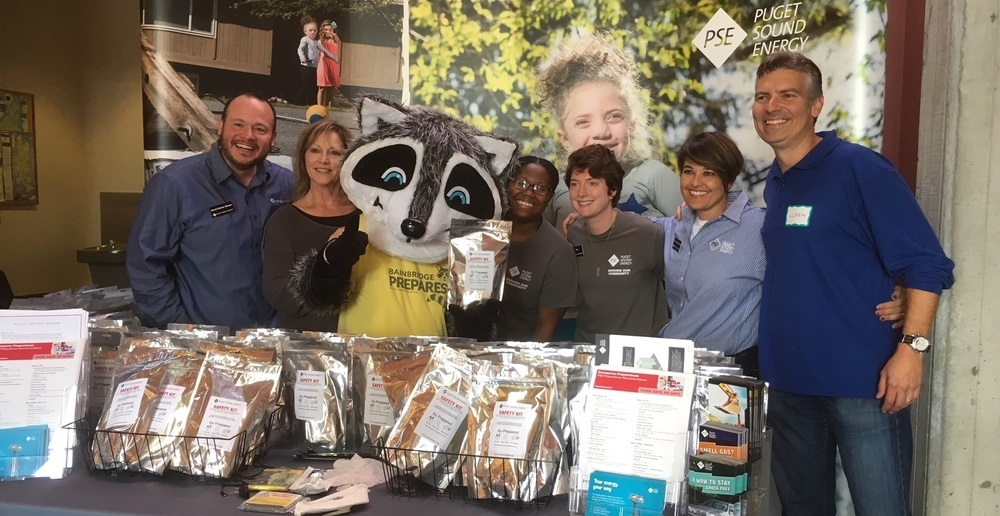 PSE staff with Ready Raccoon at the Expo Day standing behind a table of brochures and packaged food.