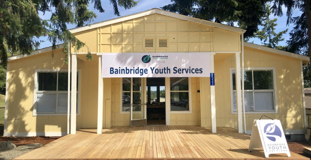 A yellow building with an extended porch, a banner outside of the house reads: Bainbridge Youth Services