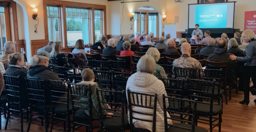 Attendees at a community meeting on the Crystal Springs/Point White project view a presentation from PSE's Renee Zimmerman.