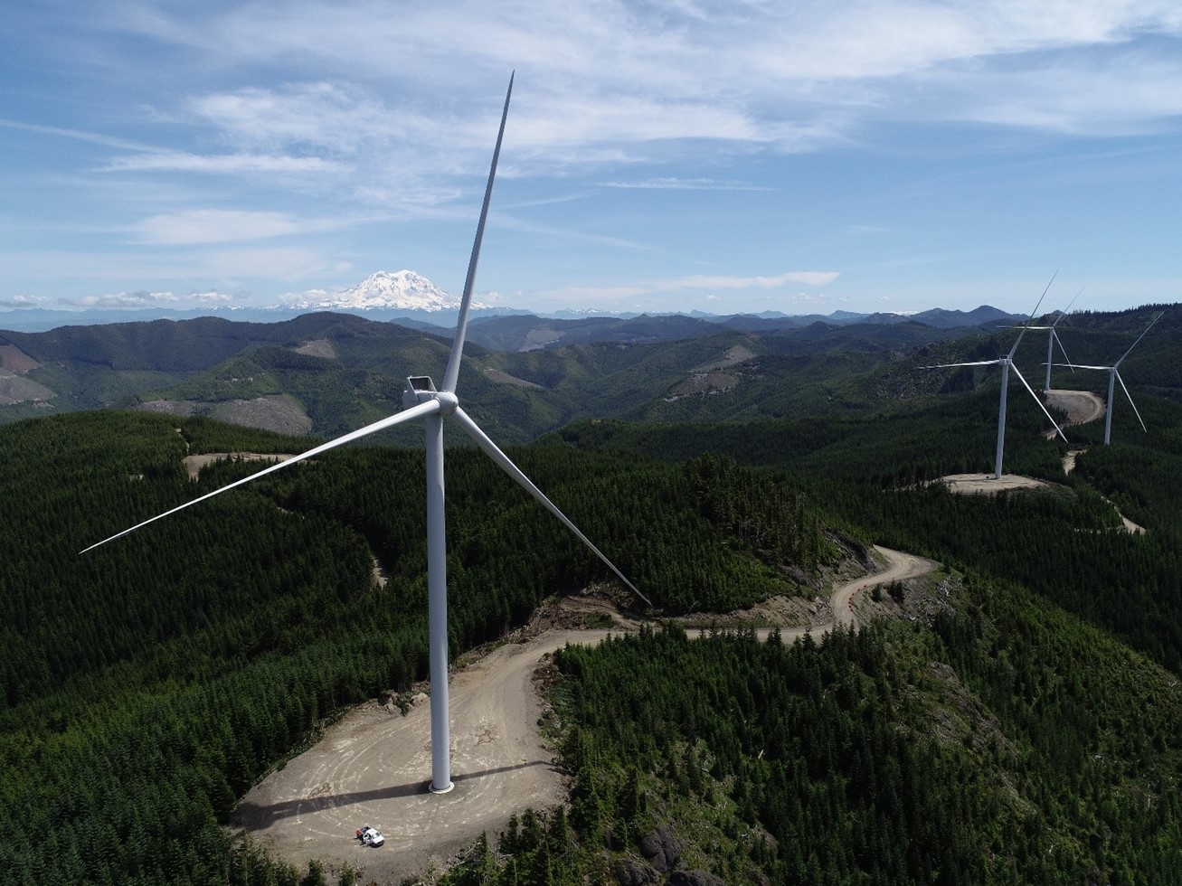 A single wind turbine on a hill surrounded by trees. A mount is the background of the picture.