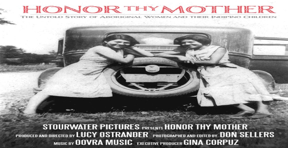 Two women pose behind car trunk.