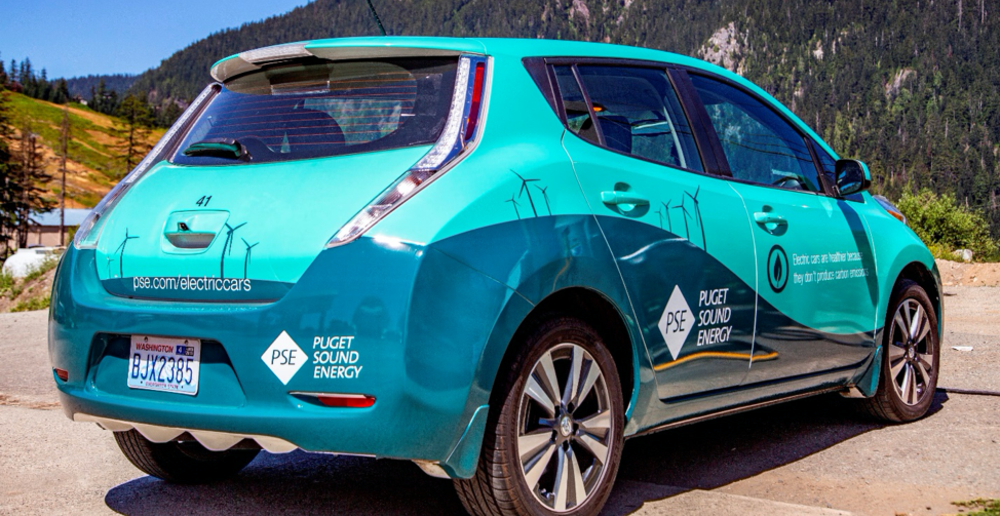 A PSE branded Nissan Leaf electric vehicle is parked in front of mountains, with a clear blue sky in the background.