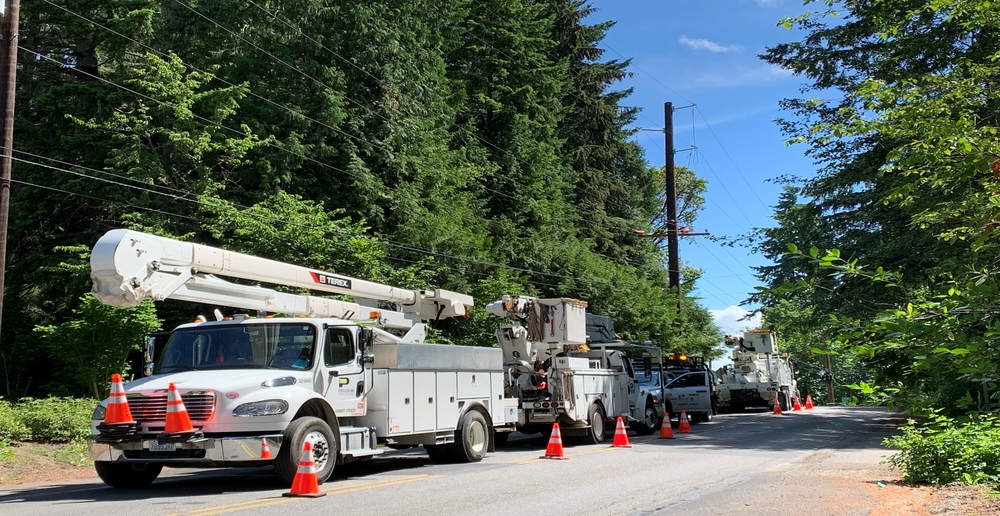 Three PSE service utility trucks parked in a closed lane of traffic.