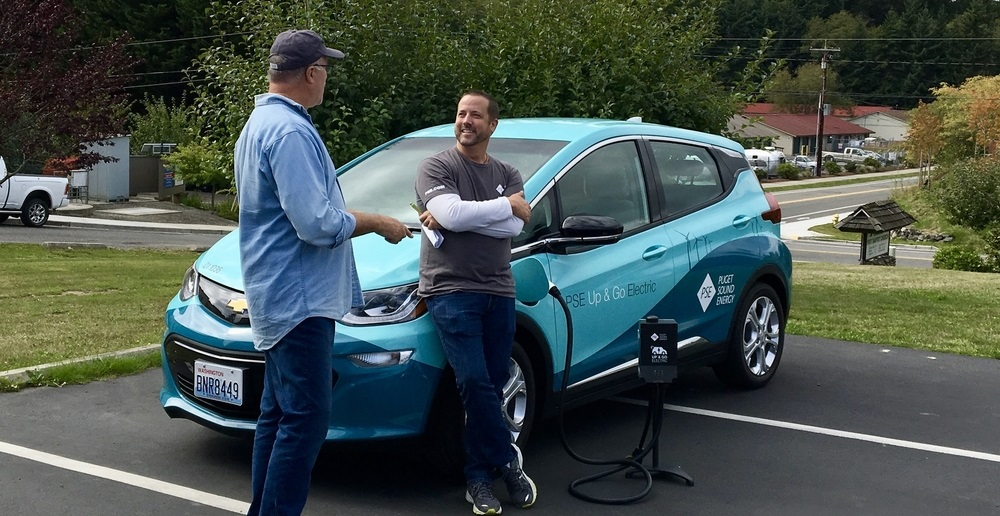 Two men are talking to each other and standing next to an electric vehicle