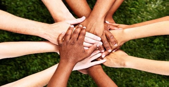 Hands in the center of the photo in a huddle with all the hands stacked on top of each other. The hands belong to people of different races.