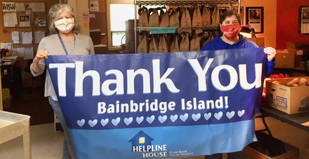 """Two members of Helpline House holding up a """"Thank You"""" banner"""