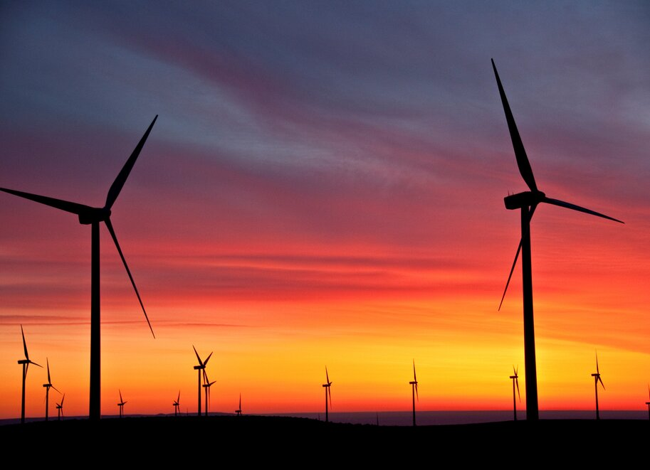 Wind turbines at PSE's Wild Horse wind and solar facility. The wind turbines are pictured against a sunset.