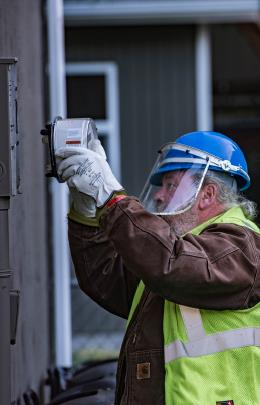 A man wearing a face shield and construction vest is putting a mter onto a house.