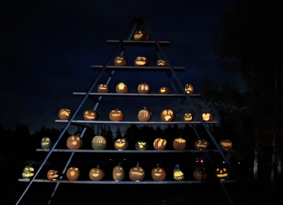 A pyramid of jack-o'-lanterns that are all lit up.