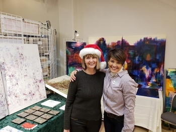 Artist Deborah Rhee and PSE's Renee Zimmerman pose for a photo near Deborah's artwork.